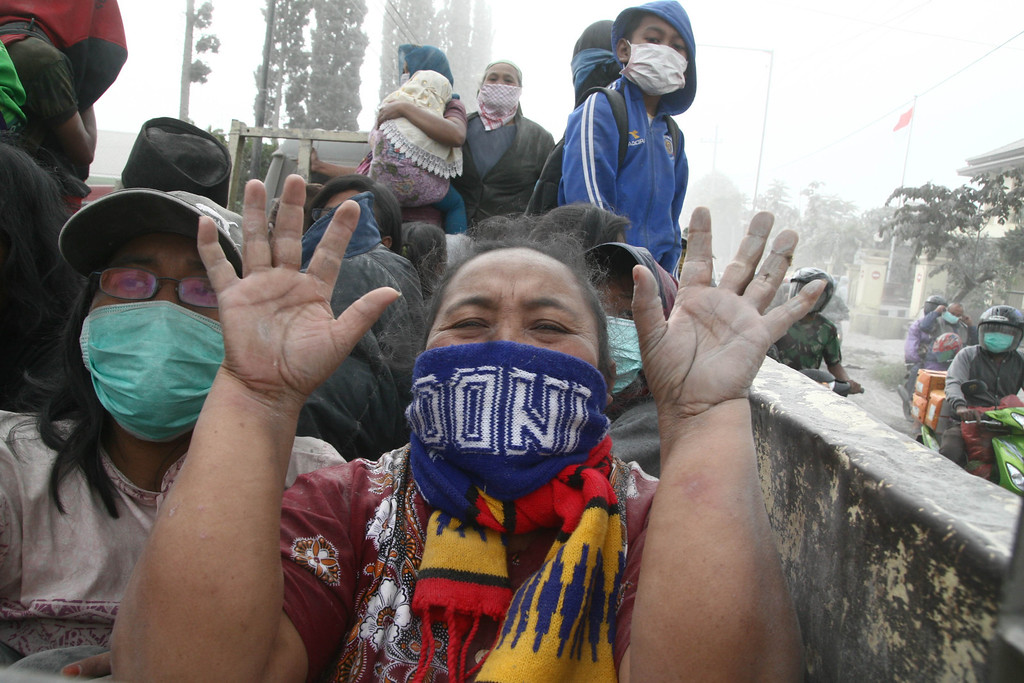 . A woman gestures during the evacuation in Malang, East Java province, on February 14, 2014 moment after Mount Kelud eruption. Hundreds of thousands of Indonesians were ordered to evacuate after a volcano, the 1,731-meter Mount Kelud, on the main island of Java erupted spectacularly, hurling red hot ash and rocks over a huge distance. AFP PHOTO / Aman ROCHMAN/AFP/Getty Images