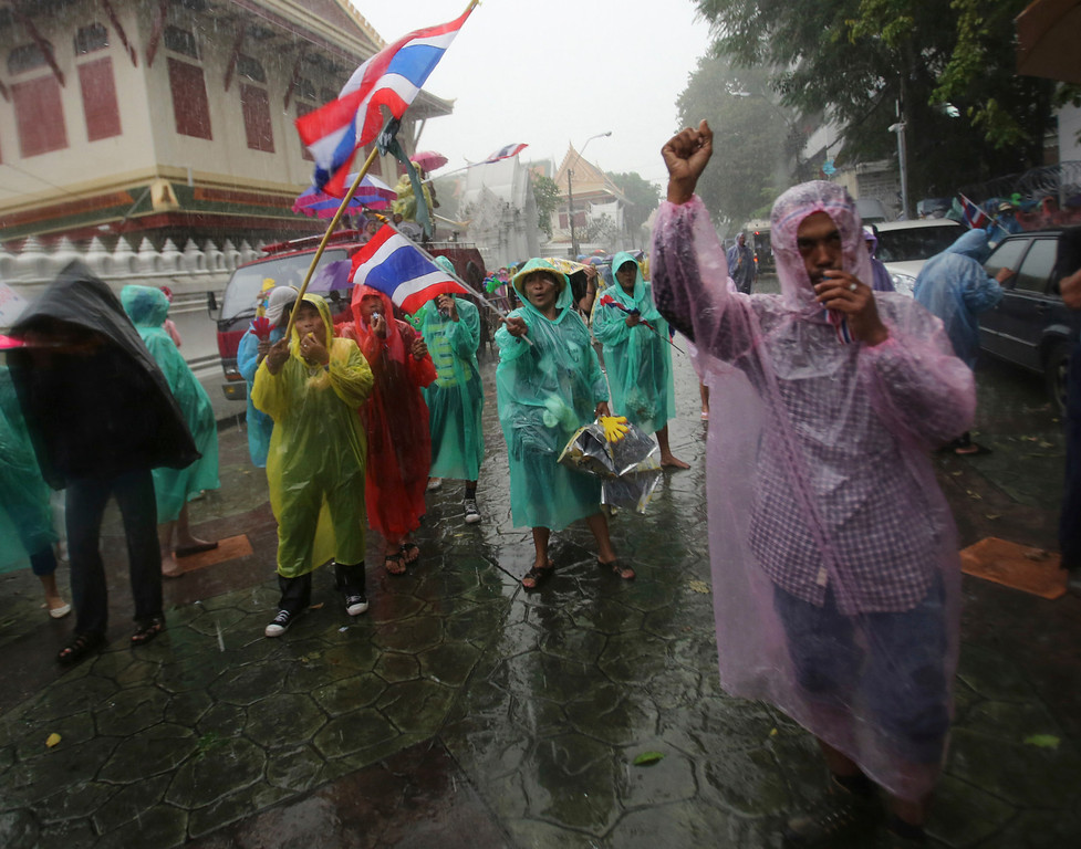 . Braving the rain, anti-government protesters stage a rally outside Interior Ministry in Bangkok, Thailand, Tuesday, Nov. 26, 2013. (AP Photo/Sakchai Lalit)