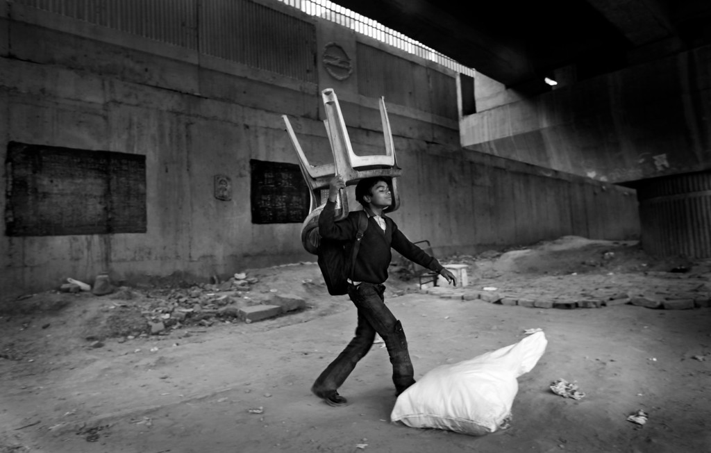 . In this Dec. 11, 2012 photo, an underprivileged Indian boy tries to lift a sack containing mats while carrying plastic chairs on his head to store them till next morning at a temporary storeroom as class ends at a free school run under a metro bridge in New Delhi, India. This photo was one in a series of images by Associated Press photographer Altaf Qadri that received an honorable mention in the World Press Photo 2013 photo contest for the Contemporary Issues series category. (AP Photo/Altaf Qadri, File)