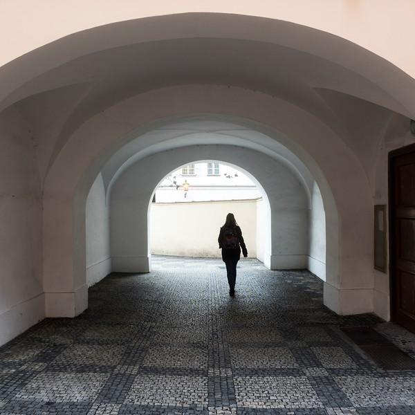 Woman walking on cobblestone street, Prague, Czech Republic