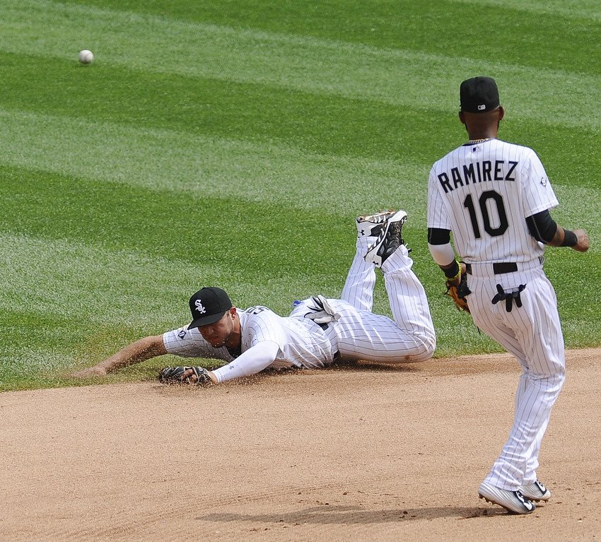 . As Chicago White Sox shortstop Alexei Ramirez looks on, Chicago White Sox second baseman Carlos Sanchez fails to catch a ball hit by Detroit Tigers Tyler Collins during the sixth inning of baseball game in Chicago on Sunday, June 7,  2015.  (AP Photo/Matt Marton)