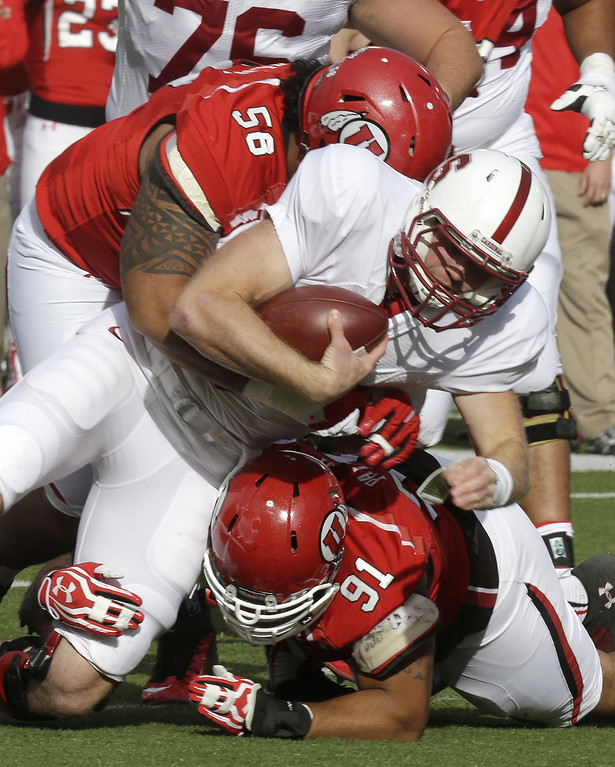 . Stanford quarterback Kevin Hogan, center, is tackled by Utah\'s LT Tuipulotu (58) and teammate Tenny Palepoi (91) during the first quarter of an NCAA college football game on Saturday, Oct. 12, 2013, in Salt Lake City. (AP Photo/Rick Bowmer)