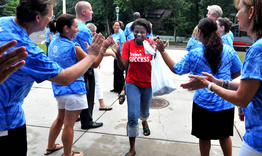 . Eighth-grader Omudalat Ajasa is greeted by faculty as she arrives at Murray Middle School in St. Paul Thursday, Aug. 29, 2013.  Middle-schoolers and their families came back early for a day of orientation and team-building activities called Camp 67. (Pioneer Press: John Doman)