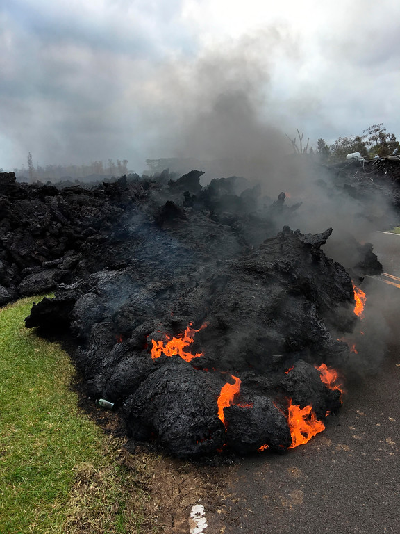 . Lava burns across the road in the Leilani Estates in Pahoa, Hawaii, Saturday, May 5, 2018. Hundreds of anxious residents on the Big Island of Hawaii hunkered down Saturday for what could be weeks or months of upheaval as the dangers from an erupting Kilauea volcano continued to grow. (AP Photo/Marco Garcia)