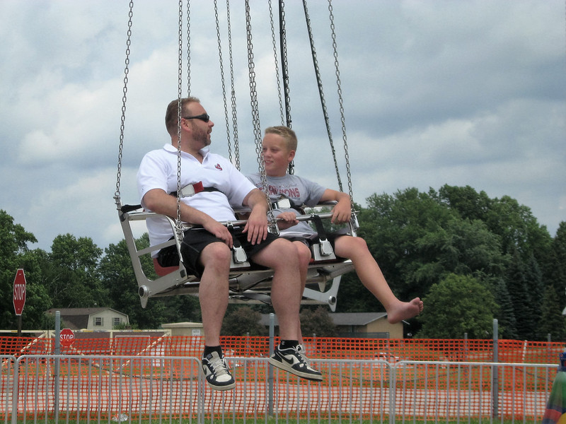 BOB SANDRICK / GAZETTE Joe Westfall and his son James, 11, of Akron take a ride on Vertigo, a circle of flying swings, on Saturday at the 2017 Summer Celebration in Brunswick.