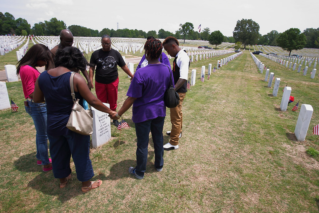. Family members of World Word II Army veteran Floyd Wiley  pray around his grave marker and that of his wife, Florence Wiley, on Memorial Day at West Tennessee Veterans Cemetery in Memphis, Tenn. Monday, May 26, 2014. (AP Photo/The Commercial Appeal, Mike Brown)