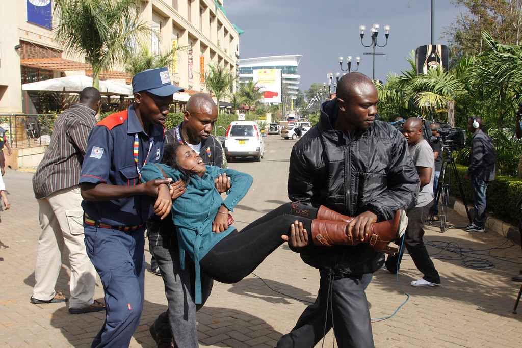 . A security officer helps a wounded woman outside the Westgate Mall in Nairobi, Kenya Saturday, Sept. 21, 2013, after gunmen threw grenades and opened fire during an attack that left multiple dead and dozens wounded.  (AP Photo/Khalil Senosi)