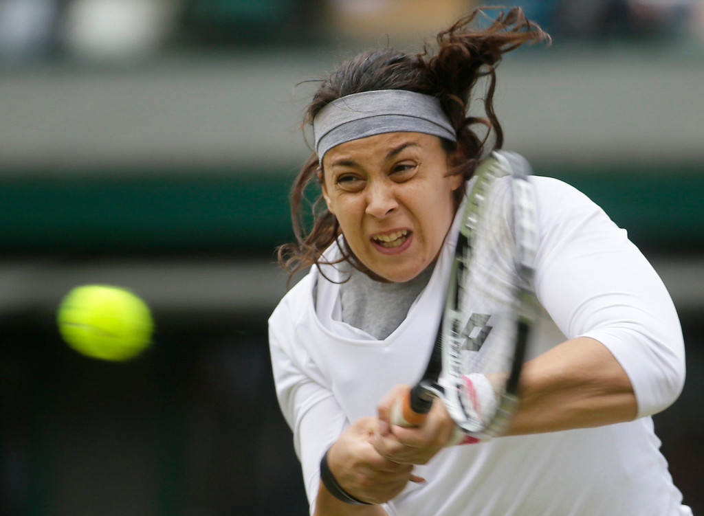 . Marion Bartoli of France plays a return to Sloane Stephens of the United States during their Women\'s singles quarterfinal match at the All England Lawn Tennis Championships in Wimbledon, London, Tuesday, July 2, 2013. (AP Photo/Alastair Grant)