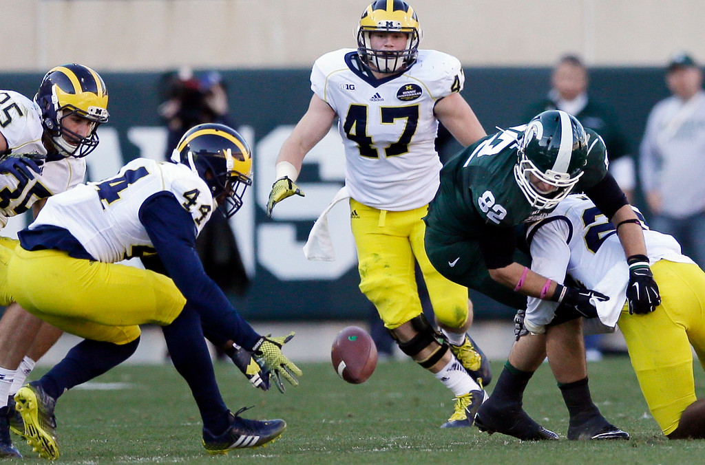 . Michigan defensive back Delano Hill (44) picks up the ball fumbled by Michigan State tight end Josiah Price (82) during the first half of an NCAA college football game in East Lansing, Mich., Saturday, Oct. 25, 2014. (AP Photo/Carlos Osorio)