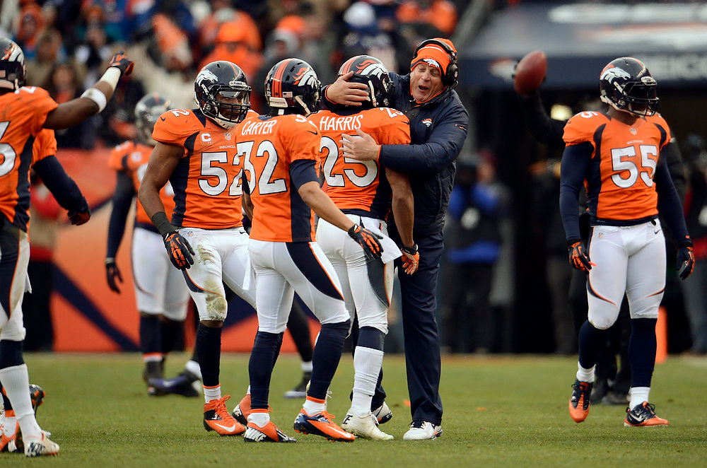 . Broncos Defensive Coordinator Jack Del Rio hugs Denver Broncos cornerback Chris Harris (25) after Harris broke up a pass intended for Denver Broncos tight end Joel Dreessen (81) during the first half.  The Denver Broncos vs Baltimore Ravens AFC Divisional playoff game at Sports Authority Field Saturday January 12, 2013. (Photo by John Leyba,/The Denver Post)