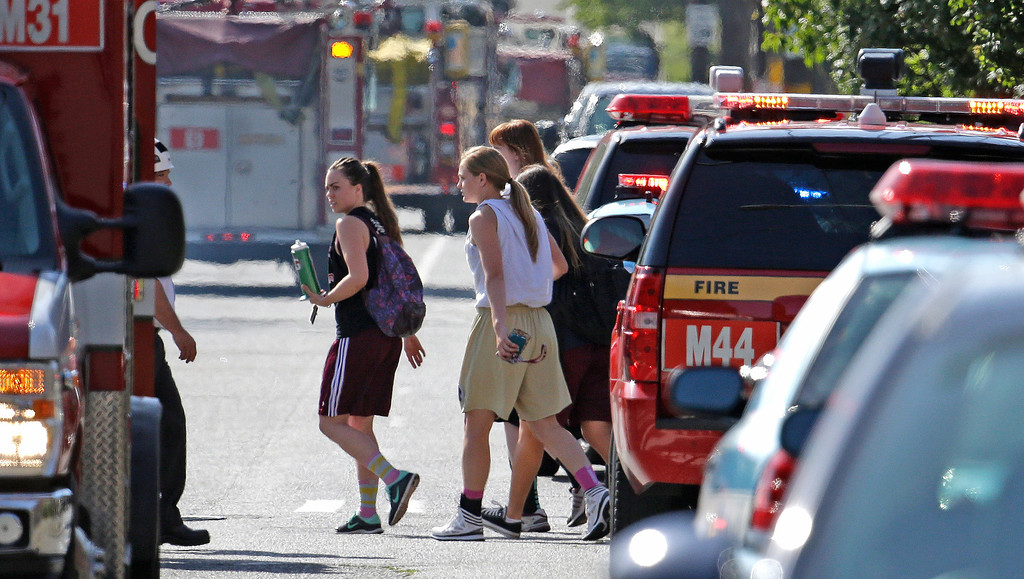 . A group of young people walk away past emergency vehicles near the scene of a shooting at Seattle Pacific University on Thursday, June 5, 2014, in Seattle. A lone gunman armed with a shotgun opened fire in a building on the campus, killing one person before he was subdued by a student as he tried to reload, police said. Police say the student building monitor at the university disarmed the gunman and several other students held him until police arrived at the Otto Miller building. (AP Photo/Elaine Thompson)