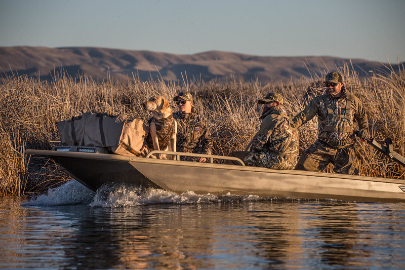 Duck boat with dog and hunters
