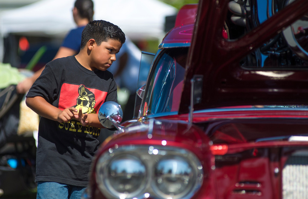 """. IDB-L-DBROUTE66-SAT-02 Gilbert Munoz, 6, of Ontario Checks out a customized 1958 Chevy Impala  . Classic cars line Euclid Ave in Ontario, for the  \"""" Route 66 Cruisin� Reunion\"""", on Saturday, September 21, 2013. (photos by Frank Perez for the Daily Bulletin)"""
