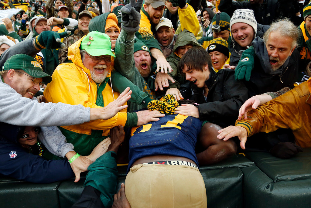 . Fans celebrate with Green Bay Packers\' Eddie Lacy after his touchdown run during the first half of an NFL football game against the Cleveland Browns Sunday, Oct. 20, 2013, in Green Bay, Wis. (AP Photo/Tom Lynn)