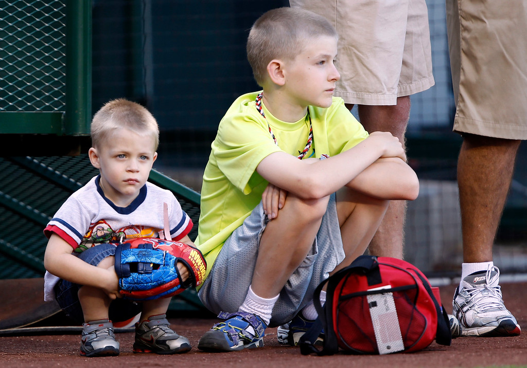 . Three-year-old Landon Pegg and his ten-year-old brother Danny Pegg take in batting practice of the Los Angeles Angels prior to a baseball game against the Seattle Mariners Tuesday, May 21, 2013 in Anaheim.    (AP Photo/Alex Gallardo)