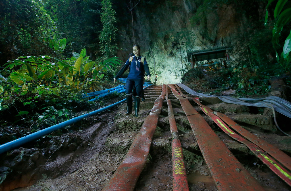 . A rescuer makes her way down muddy steps past water pump hoses at the entrance to a cave complex where it\'s believed that 12 soccer team members and their coach went missing, Friday, June 29, 2018, in Mae Sai, Chiang Rai province, in northern Thailand. (AP Photo/Sakchai Lalit)