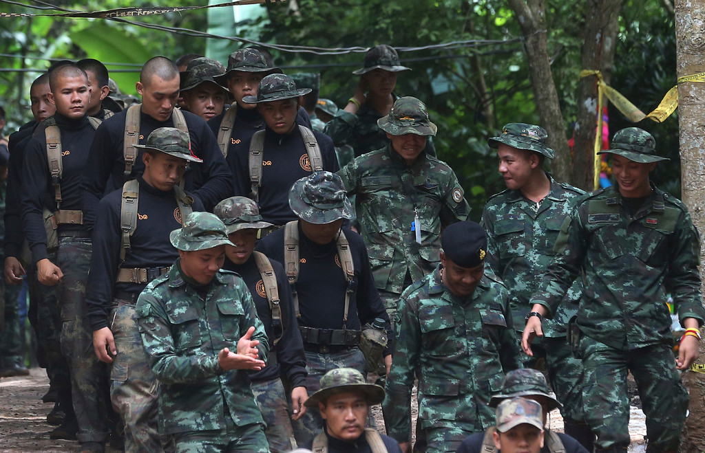 . Thai soldiers makes their way down at the entrance to a cave complex where 12 boys and their soccer coach were trapped inside when heavy rains flooded the cave, in Mae Sai, Chiang Rai province, in northern Thailand, Wednesday, July 4, 2018. The Thai soccer teammates stranded more than a week in a partly flooded cave said they were healthy on a video released Wednesday, as heavy rains forecast for later this week could complicate plans to safely extract them. (AP Photo/Sakchai Lalit)