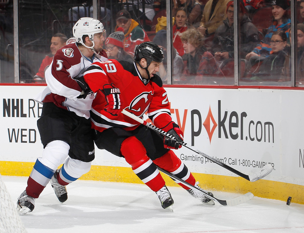 . Nate Guenin #5 of the Colorado Avalanche checks Ryane Clowe #29 of the New Jersey Devils during the second period in an NHL hockey game at Prudential Center on February 3, 2014 in Newark, New Jersey.  Colorado won 2-1 in overtime.  (Photo by Paul Bereswill/Getty Images)