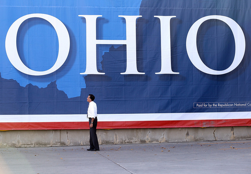 . Republican presidential candidate, former Massachusetts Gov. Mitt Romney looks at a large banner during a campaign rally at Worthington Industries on October 25, 2012 in Cincinnati, Ohio. Mitt Romney is campaigning in Ohio with less than two weeks to go before the election.  (Photo by Justin Sullivan/Getty Images)
