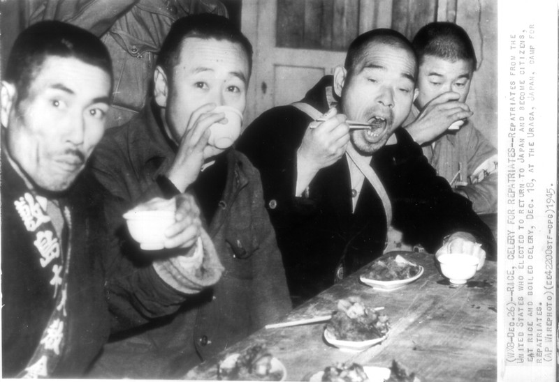 """""""Rice, Celery for Repatriates -- Repatriates from the United States who elected to return to Japan and become citizens, eat rice and boiled celery, Dec. 18, at the Uraga, Japan, camp for repatriates.""""--caption on photograph"""