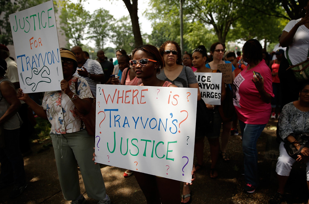 """. WASHINGTON, DC - JULY 20:  Protesters take part in a \""""Justice for Trayvon\"""" vigil outside the E. Barrett Prettyman Federal Courthouse July 20, 2013 in Washington, DC. The vigil, along with others held nationwide, was organized by the National Action Network and called for federal charges to be filed against George Zimmerman in the shooting death of teenager Trayvon Martin.  (Photo by Win McNamee/Getty Images)"""