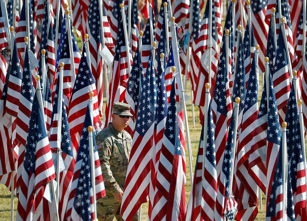 . A U.S. Army soldier walks through rows of nearly 3,000 flags with the names of those who died in the Sept. 11, 2001 terror attacks, Tuesday, Sept. 11, 2018, at Tempe Beach Park in Tempe, Ariz.  (AP Photo/Matt York)