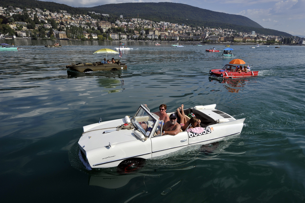 Description of . Amphibious cars motor across Lake Neuchatel on August 18, 2011 near Saint-Blaise during the 26th meeting of amphibious car. This week, owners of more than 50 of these amphibious vehicles brought their World War 2-era military transporters, jeeps and vintage-style cars to Switzerland's St Blaise for their annual European gathering. Fitted with colourful sun umbrellas and decorated with flags, what looked like a motley crew of vehicles carrying families including babies and dogs drove off the port and glided smoothly into the water, before moving across Lake Neuchatel.   AFP PHOTO / FABRICE COFFRINI