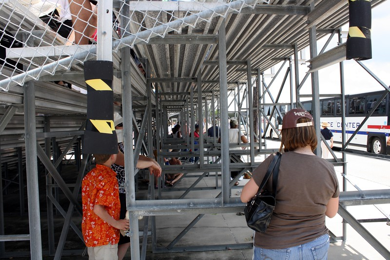 Guests wait for the launch in the shade under the bleachers