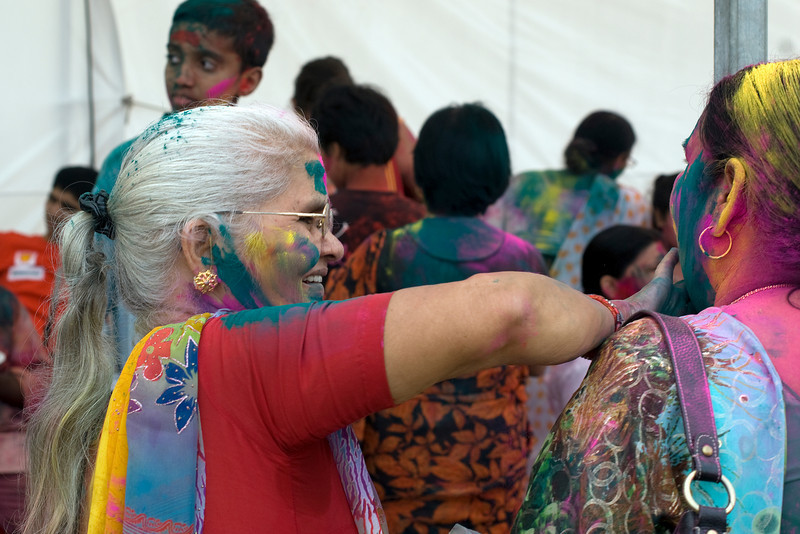 Woman wiping color powder off another's face at Singapore's Festival of Colors