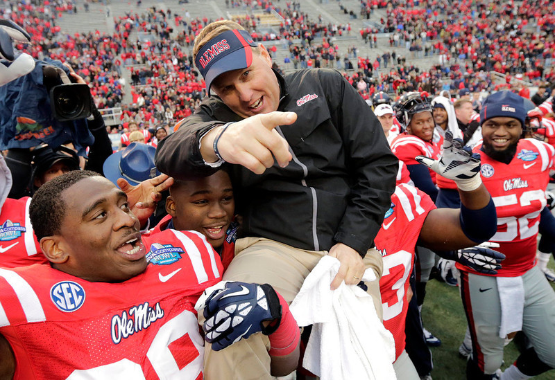 . Mississippi head coach Hugh Freeze is hoisted by his players Jason Jones (38) and  Uriah Grant (93) at the end of the BBVA Compass Bowl NCAA college football game against Pittsburgh at Legion Field in Birmingham, Ala., Saturday, Jan. 5, 2013. Mississippi won 38-17. (AP Photo/Dave Martin)
