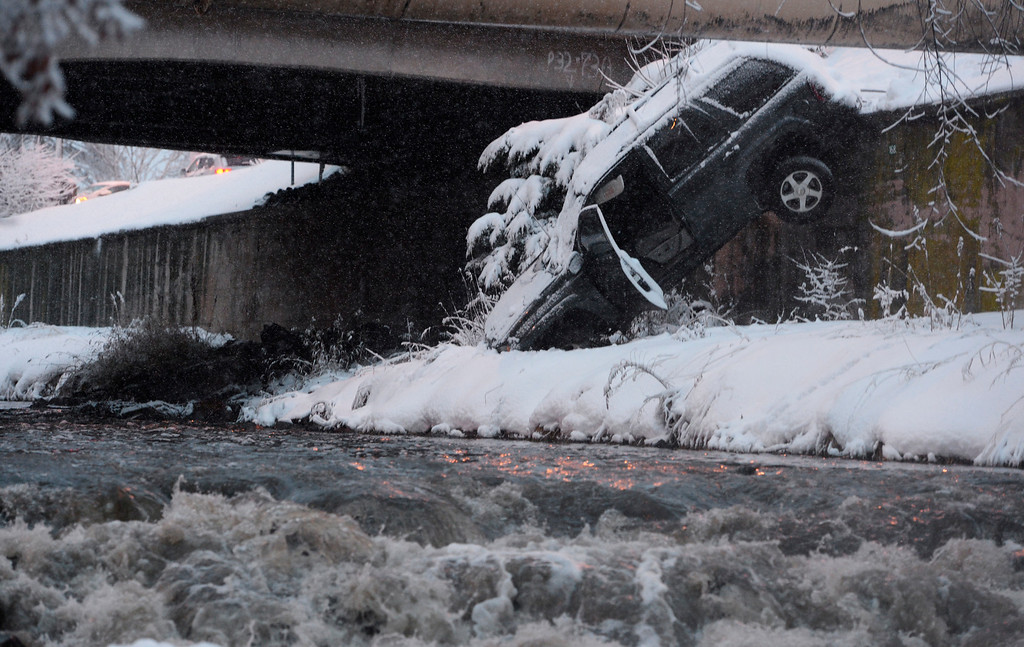 . DENVER, CO - February 25: A SUV sits on the edge of Cherry Creek on Wednesday, February 25, 2015 at intersection of Speer Boulevard and Downing Street in Denver, Colorado. Close to 4:00PM a driver lost control of his car and the car went into Cherry Creek. There was no injuries reported and a two crew was able to pull the car out of the creek.(Photo By Brent Lewis/The Denver Post)