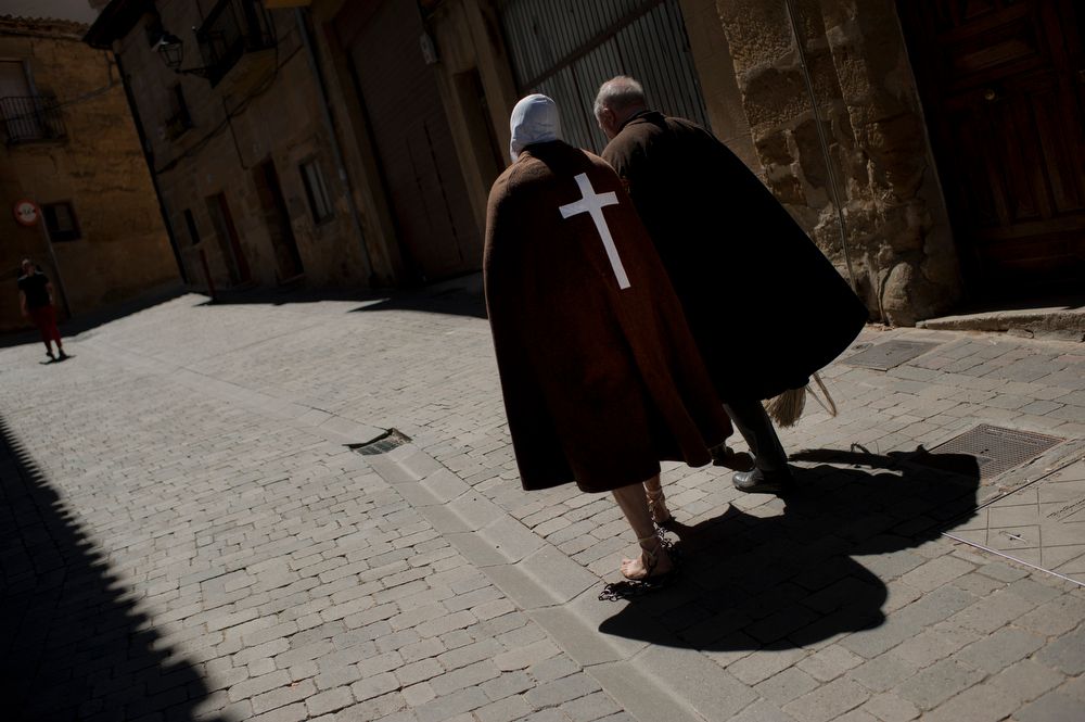 . Masked penitent from La Santa Vera Cruz brotherhood walks with his assistant taking part in an Easter procession known as \'Los Picaos\' in the small village of San Vicente de la Sonsierra, northern Spain, Friday, April 18, 2014. Penitents, or disciplinants, take part on the procession lashing themselves as an act of faith and penance, a tradition dating from the early 16th century. (AP Photo/Alvaro Barrientos)
