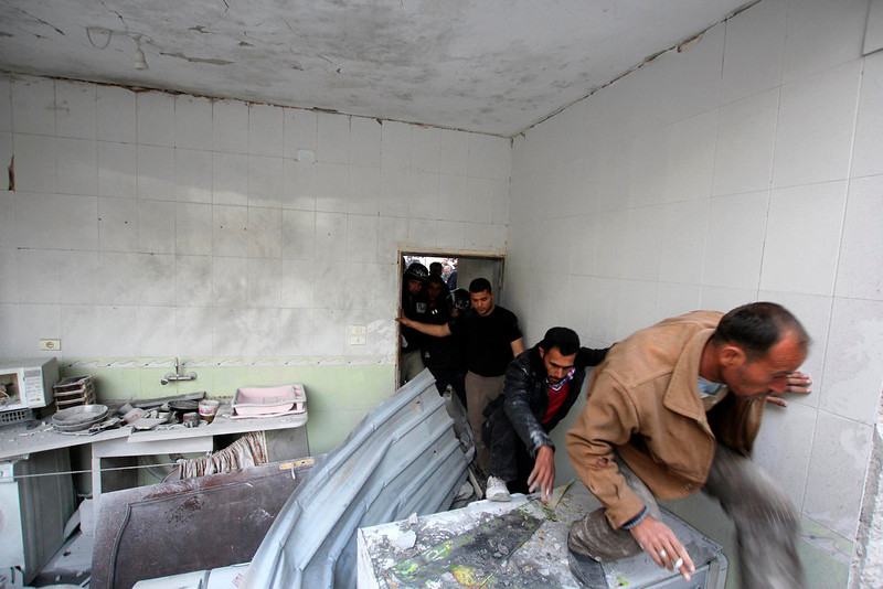 . Civilians search for casualties inside a building, which activists said was damaged after it came under fire by a Syrian Air Force fighter jet loyal to Syria\'s President Bashar al-Assad, in Kefr Hamra area, north of Aleppo March 19, 2013. Picture taken March 19, 2013. REUTERS/Giath Taha
