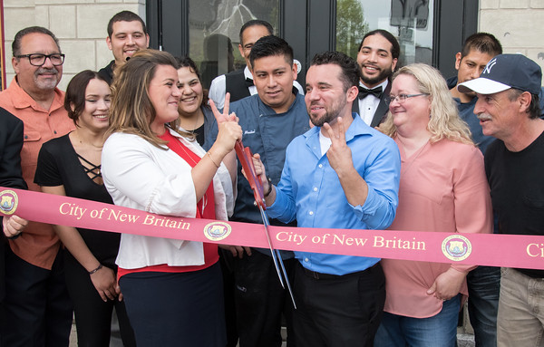 05/17/18 Wesley Bunnell | Staff Vincent Placeres held a ribbon cutting for his newest restaurant The Kitchen on Thursday afternoon down the street from Mofongo Restaurant which he opened in 2017. Mayor Erin Stewart and Placeres make the number two sign signifying his second restaurant opened in New Britain.