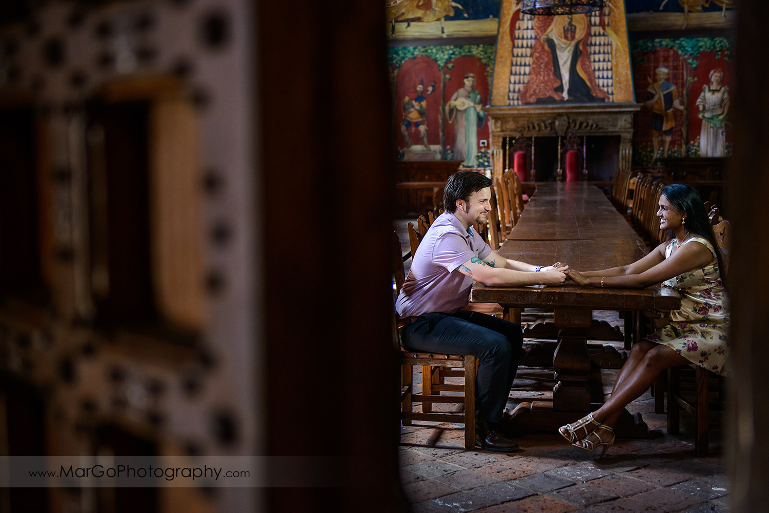 man in pink shirt and Indian woman in flower dress holding hands and sitting at the big wooden table during engagement session at Castello di Amorosa in Calistoga
