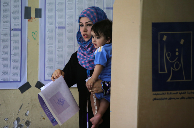 Description of . An Iraqi woman carrying her child votes at a polling station in Baghdad's Sadr City district during the country's general elections on April 30, 2014. Iraqis streamed to voting centres nationwide, amid the worst bloodshed in years, as Prime Minister Nuri al-Maliki seeks reelection. (AHMAD AL-RUBAYE/AFP/Getty Images)