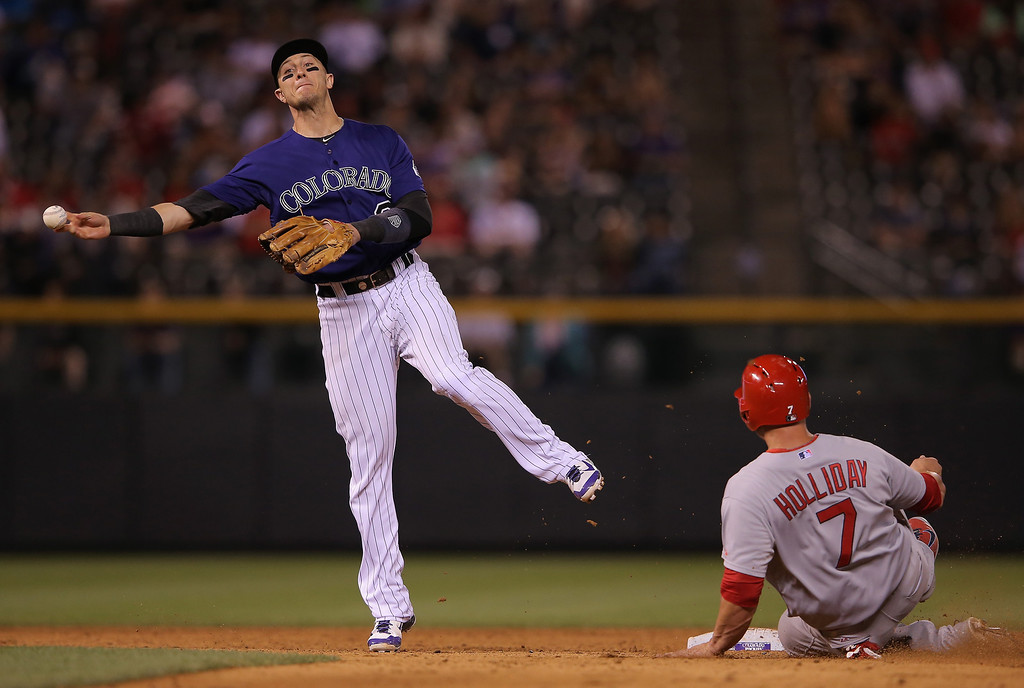 . Shortstop Troy Tulowitzki #2 of the Colorado Rockies turns a double play on Matt Holliday #7 of the St. Louis Cardinals on a ground ball by Matt Adams #32 of the St. Louis Cardinals in the ninth inning at Coors Field on June 23, 2014 in Denver, Colorado.  (Photo by Doug Pensinger/Getty Images)
