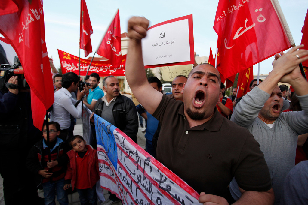 """. Activists from the Jordanian Communist Party and other parties, chant anti-U.S. slogans, during a protest in front of the U.S. embassy against the upcoming visit by President Barack Obama to the kingdom, in Amman, Jordan, Thursday, March 21, 2013.  Arabic on the U.S. flag reads, \""""down with the mother of all imperialisms, the enemy of people, the head of the backward and the torture.\""""  (AP Photo/Mohammad Hannon)"""