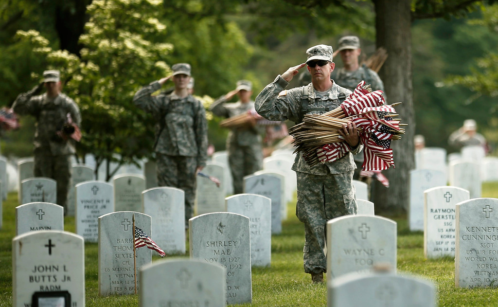 """. Soldiers salute as \""""Taps\"""" is played during a military funeral nearby as they were placing flags on graves at Arlington National Cemetery in Virginia May 23, 2013. The annual \""""Flags-In\"""" ceremony is held ahead of Memorial Day to honor the nation\'s fallen members of the military. Soldiers of the Third U.S. Infantry Regiment (The Old Guard) place a small American flag before each grave marker for more than 220,000 graves.    REUTERS/Kevin Lamarque"""