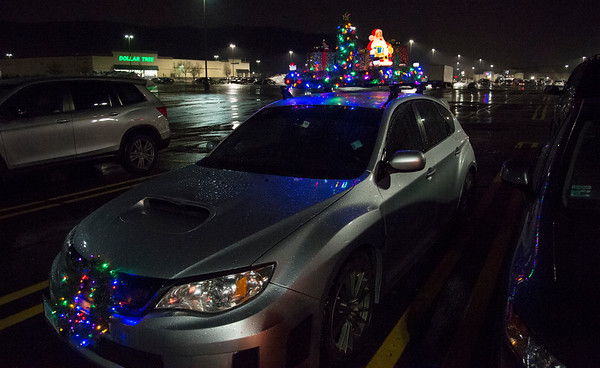 12/09/19 Wesley Bunnell | StaffrrA car featuring Christmas decorations on its roof racks sits outside of the movie theater in Plainville on a rainy Monday night December 9, 2019.