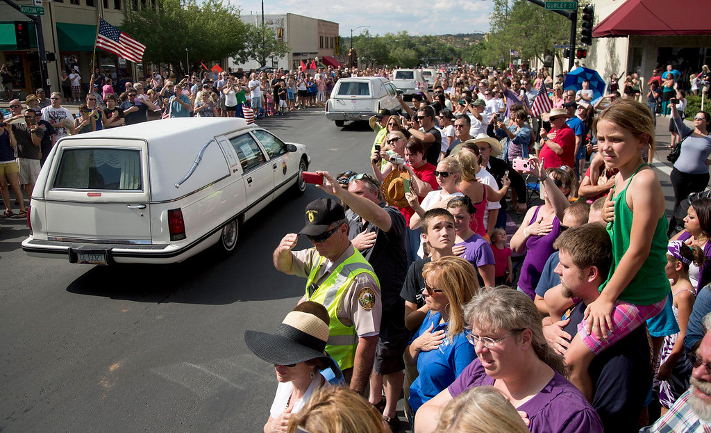 . Hundreds of people line Montezuma Street Sunday, July 7, 2013 in downtown Prescott, Ariz. to pay respects as 19 hearses slowly roll by carrying the 19 Granite Mountain Hotshot firefighters killed a week ago by an out-of-control blaze near Yarnell, Ariz. The nearly five-hour-long procession began near the state Capitol in Phoenix, went through the town where the Granite Mountain Hotshots were killed and ended in the mountain community of Prescott, where they lived and will be laid to rest this week. (AP Photo/Julie Jacobson)