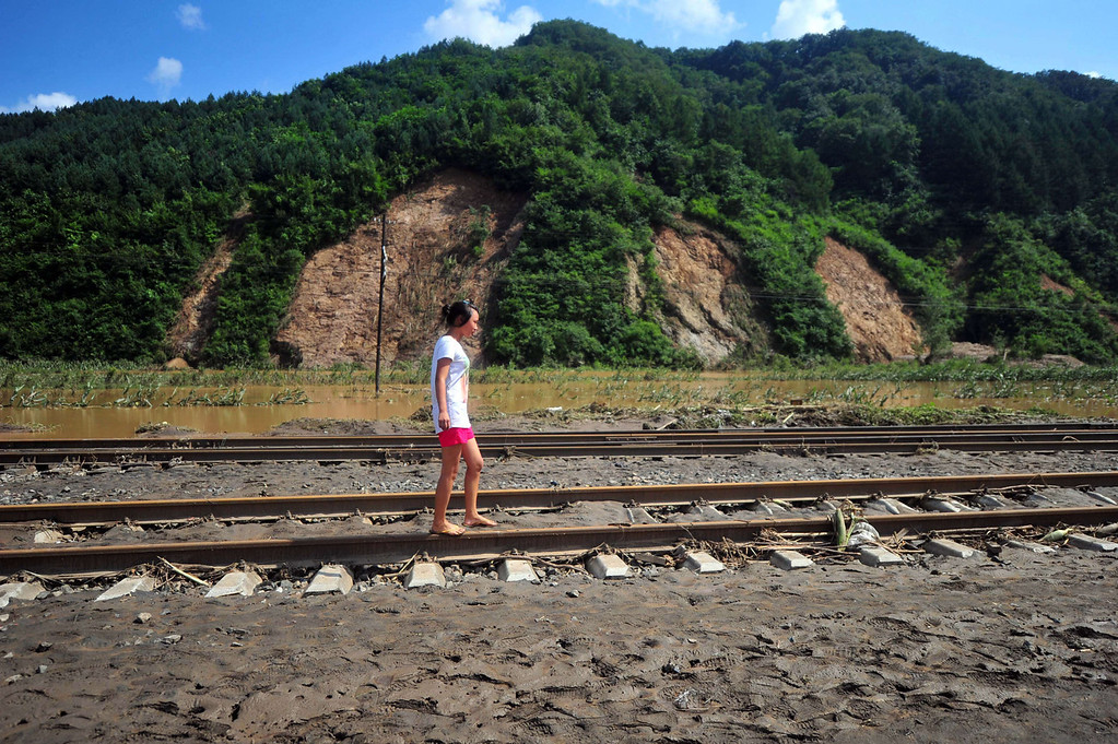 """. A girl walking barefoot on train track covered with mud after floods hit the Qingyuan Manchu autonomous county of Fushun, in northeast China\'s Liaoning province on August 18, 2013. Devastating floods at opposite ends of China have left 105 people dead and another 115 missing in recent days, state media said on August 19. Flooding in the northeast which left 72 people dead was described as \""""the worst in decades\"""" by the state news agency, while another 33 people died in the south as a result of the weather, it said citing the ministry of civil affairs.   AFP PHOTOSTR/AFP/Getty Images"""