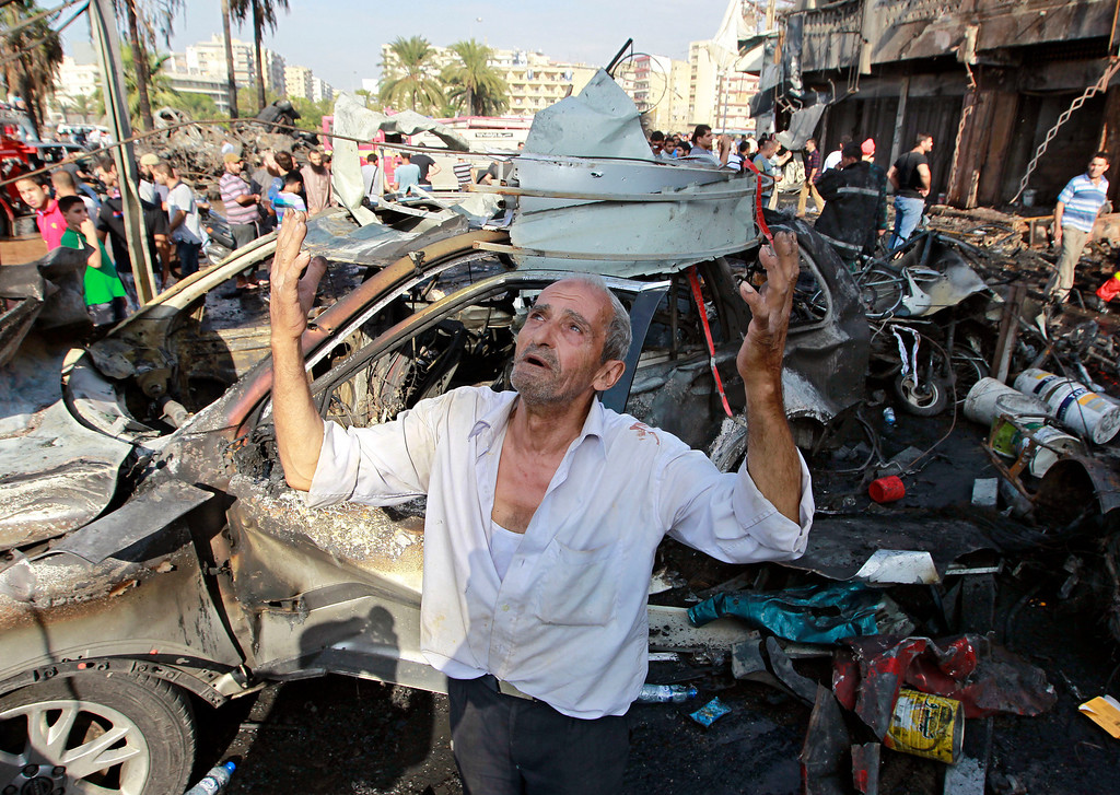 . A man recites prayers amid the destruction after a car bomb outside the Al-Taqwa mosque in the northern city of Tripoli, Lebanon, Friday, Aug. 23, 2013. The twin car bombs, which killed dozens hit amid soaring tensions in Lebanon as a result of Syria\'s civil war, which has sharply polarized the country along sectarian lines and between supporters and opponents of the regime of Syrian President Bashar Assad. It was the second such bombing in just over a week, showing the degree to which the tiny country is being consumed by the raging war next door. (AP Photo/Bilal Hussein)