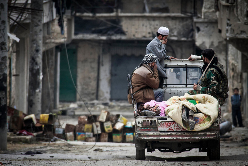 . In this Monday, Dec. 10, 2012 photo, Free Syrian Army fighters cover two dead bodies they found between rubble during heavy clashes with government forces in Aleppo, Syria. (AP Photo/Narciso Contreras)