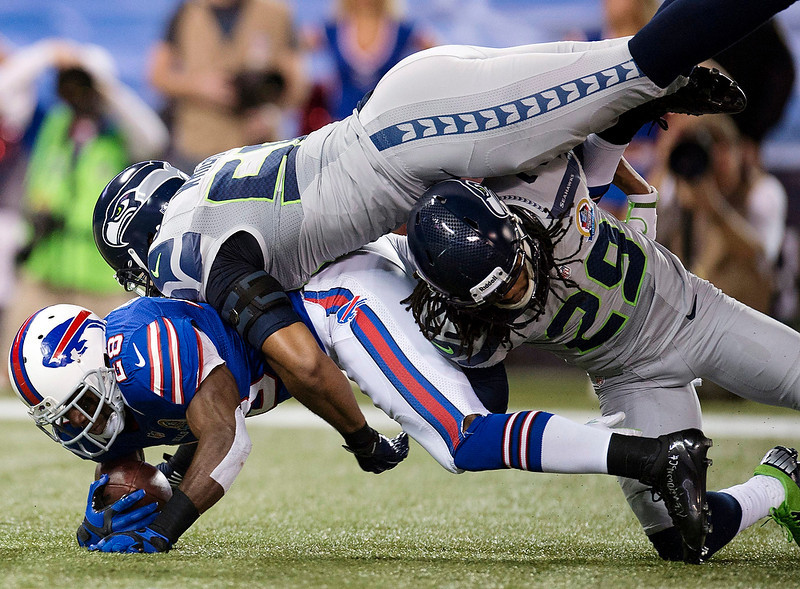 . Buffalo Bills running back C.J. Spiller (28) is tackled by Seattle Seahawks free safety Earl Thomas (29) and outside linebacker K.J. Wright (50) during the first half of an NFL football game, Sunday, Dec. 16, 2012, in Toronto. The Seahawks won 50-17. (AP Photo/The Canadian Press, Frank Gunn)