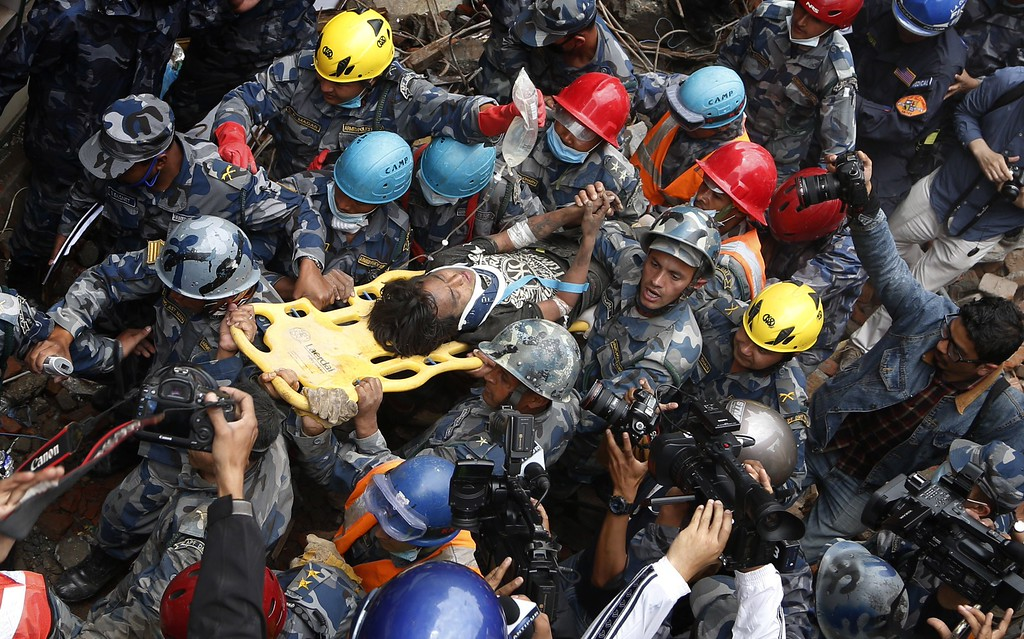 . Nepalese police personnel carry earthquake survivor Pemba Tamang (C) on a stretcher after his rescue from a destroyed hotel building in Kathmandu on April 30, 2015. Rescuers pulled a 15-year-old boy alive from the rubble of Nepal\'s earthquake April 30, bringing a rare moment of joy to the ruined capital Kathmandu, five days after a disaster which killed nearly 6,000 people. The rescue of Pemba Tamang, who told AFP that he stayed alive by eating ghee, was hailed as a miracle and greeted with cheers from crowds of bystanders who massed to watch the drama unfold at a ruined guesthouse.   AFP PHOTOSTR/AFP/Getty Images