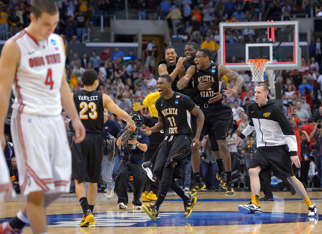 . Wichita State players celebrate their 70-66 win over Ohio State in the West Regional final in the NCAA men\'s college basketball tournament, Saturday, March 30, 2013, in Los Angeles. Ohio State guard Aaron Craft (4) walks off at left. (AP Photo/Mark J. Terrill)