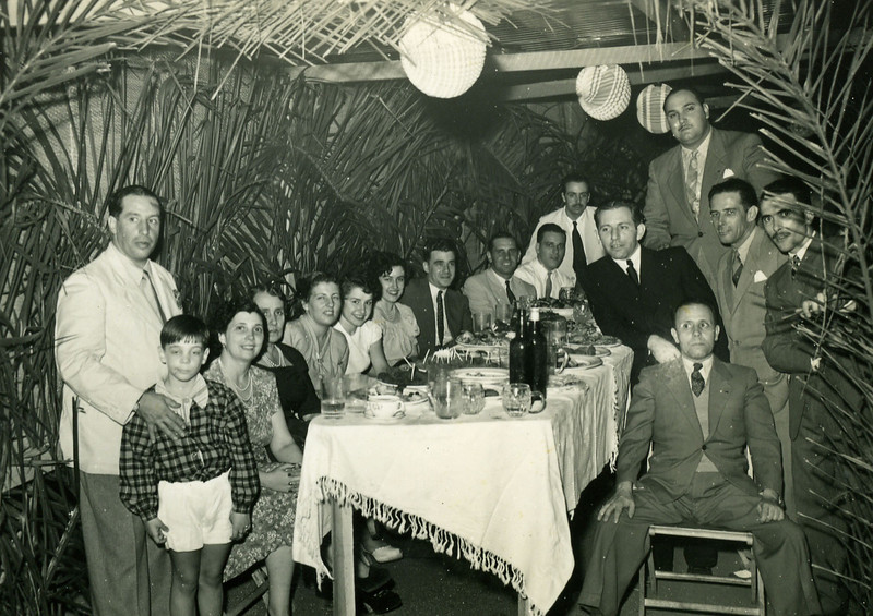 FESTA DE STº ANTÓNIO no Dundo, JUNHO 1950 Nápoles casaco cinzento e gravata, ao centro. Boal é o de bigode em pé à direita.  Adriana Nápoles parece estar ao lado do marido.Á frente, à esquerda está a família Renato Santos, do Chitato. Renato, Celeste e seu filho, Melo Abreu ao fundo de bigode.