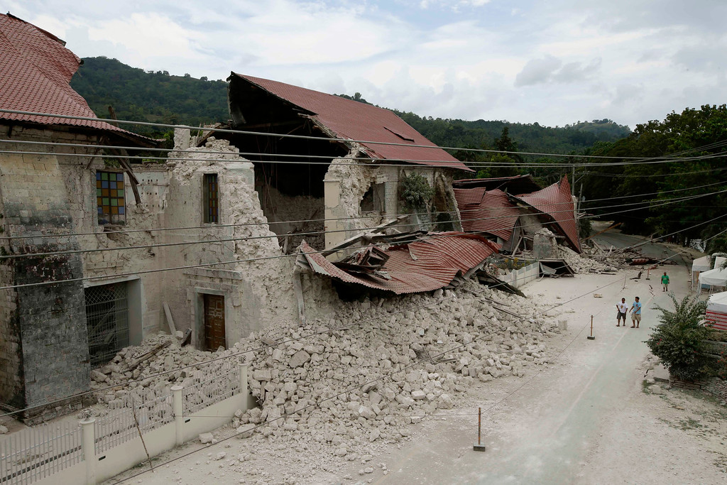 . Residents look at the collapsed Saint Peter church at Loboc township, Bohol province in central Philippines Wednesday Oct.16, 2013, a day after a 7.2-magnitude quake hit Bohol and Cebu provinces. (AP Photo/Bullit Marquez)