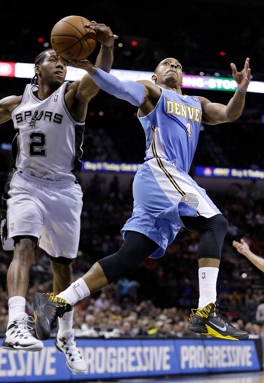. Denver Nuggets\' Randy Foye (4) is blocked by San Antonio Spurs\'  Kawhi Leonard (2) as he tries to score during the second half of an NBA basketball game, Wednesday, March 26, 2014, in San Antonio. San Antonio won 108-103. (AP Photo/Eric Gay)
